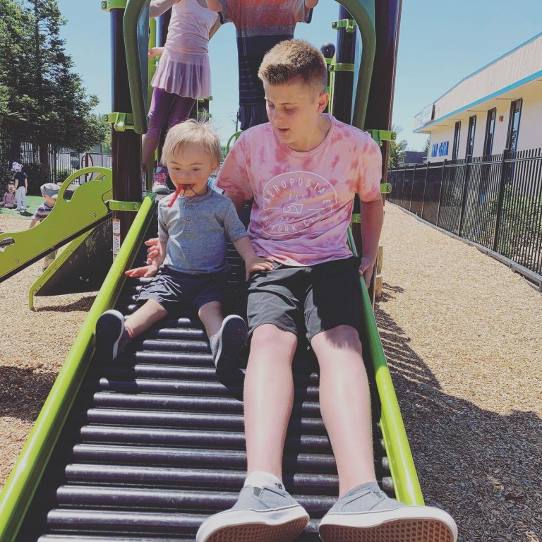 picture of a boy and his buddy going down the slide at a meet up