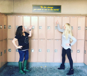"""Larkin and Melissa after their presentation at Maria Carrillo pointing to a sign that reads """"be the change you wish to see in the world"""""""